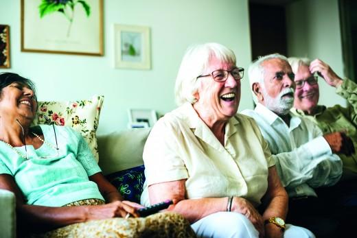 Senior people watching televison together